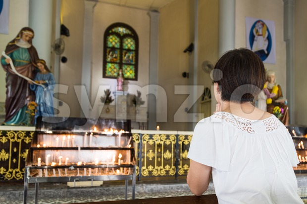 Believer kneel and praying in a Catholic church Stock Photo