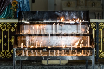 Candles station with burning candles within Catholic church Stock Photo