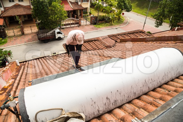 Worker fixing solar water heater on roof during maintenance Stock Photo