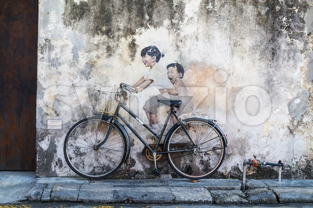 PENANG, DECEMBER 16, 2015:  Mural artwork by artist Ernest Zacharevic entitled Kids On Bicycle. The mural is located at Leboh Armenian. Stock Photo