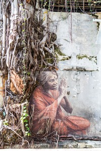 PENANG, DECEMBER 16, 2015:  Mural artwork by artist Julia Volchkova depicts an old Indian lady praying under the overgrown tree shade at Lumut lane. Stock Photo