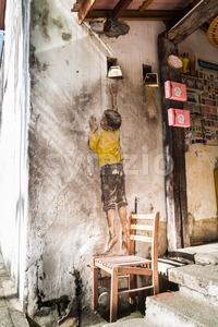 PENANG, DECEMBER 16, 2015:  Mural artwork by artist Ernest Zacharevic entitled Boy On Chair. The mural is located at Leboh Cannon. Stock Photo