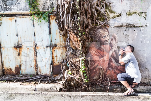 PENANG, DECEMBER 16, 2015:  A tourist posing with the mural artwork by artist Julia Volchkova of an old Indian lady praying under the overgrown tree Stock Photo