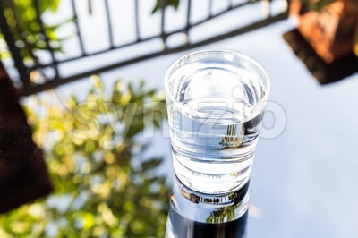 Refreshing water in transparent glass with reflection against blue sky Stock Photo