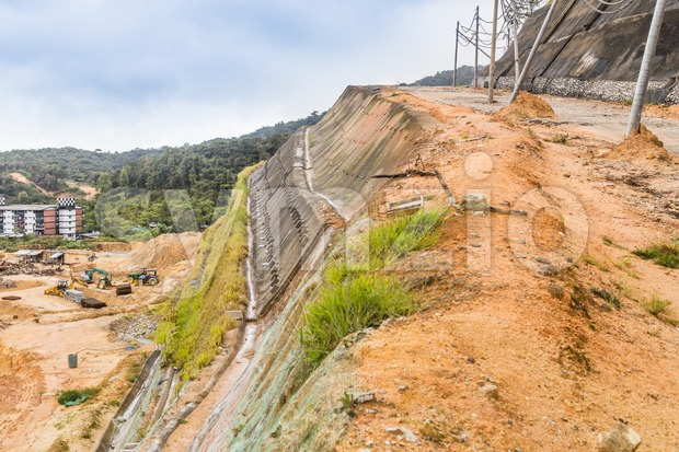 Slope and earth retention wall along hilly terrain Stock Photo