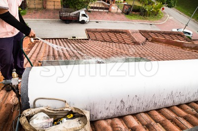 Worker cleaning solar water heater on roof during maintenance Stock Photo