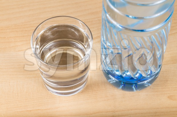 Refreshing natural mineral water in plastic bottle with transparent glass Stock Photo