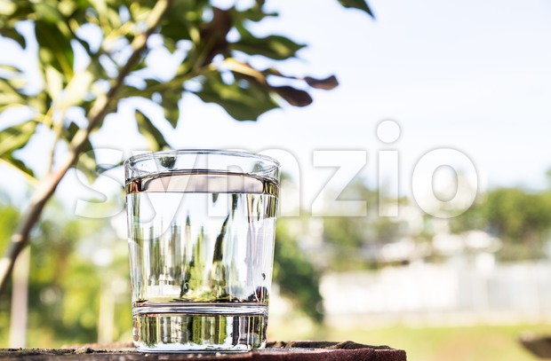 Refreshing water in transparent glass  against blue sky and greenaries Stock Photo
