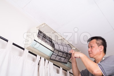 Series of technician servicing the indoor air-conditioning unit. Inspecting filter. Stock Photo