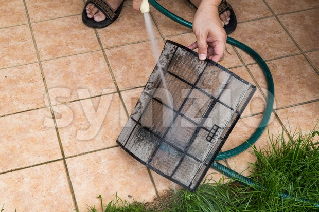 Cleaning dust filled air conditioning unit filters with with water Stock Photo