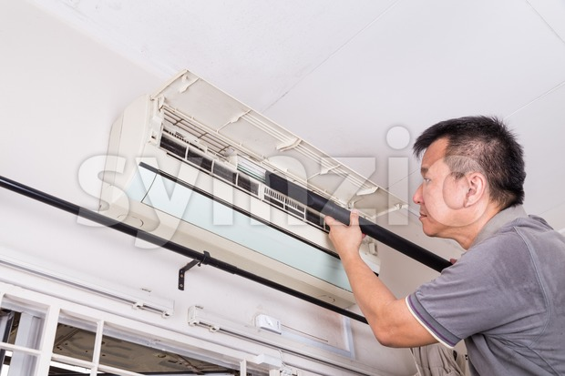 Series of technician servicing the indoor air-conditioning unit. Vacuuming. Stock Photo