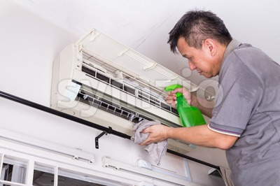 Series of technician servicing the indoor air-conditioning unit. Spray chemical. Stock Photo