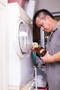 Apple cider vinegar to remove odour from washing machine dryer Stock Photo