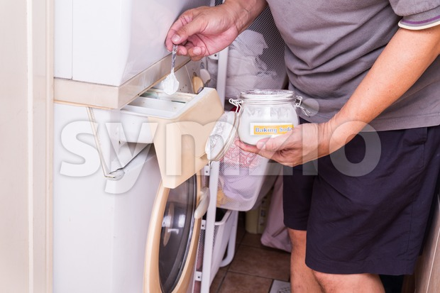 Person adding baking soda into washing machine to wash clothes for brighter and cleaner finish