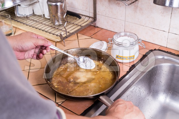 Baking soda to soak and remove burnt-on food in pans Stock Photo