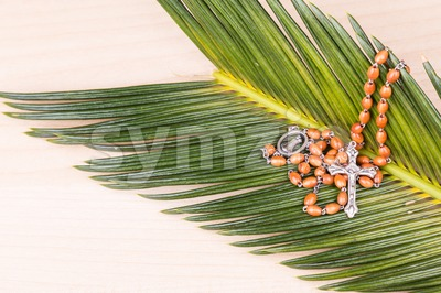 Closeup Catholic rosary with crucifix and beads on palm leaf Stock Photo