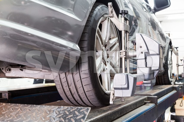 Closeup of tire clamped with aligner undergoing auto wheel alignment Stock Photo