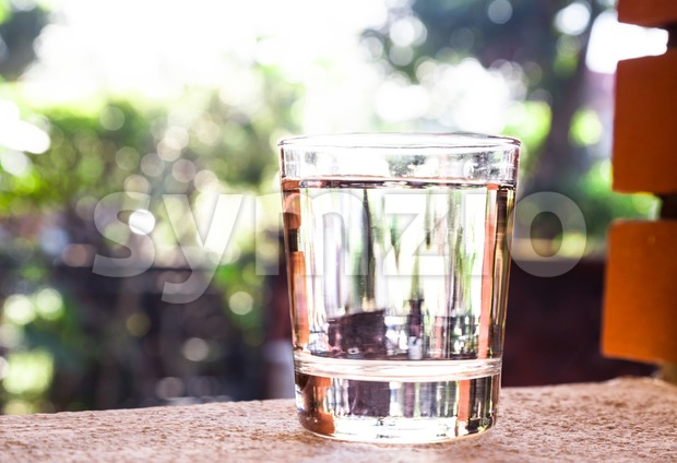 Refreshing water in transparent glass  against with greeneries background Stock Photo