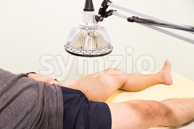 Acupuncture patient being treated with needles and infrared heat lamp Stock Photo