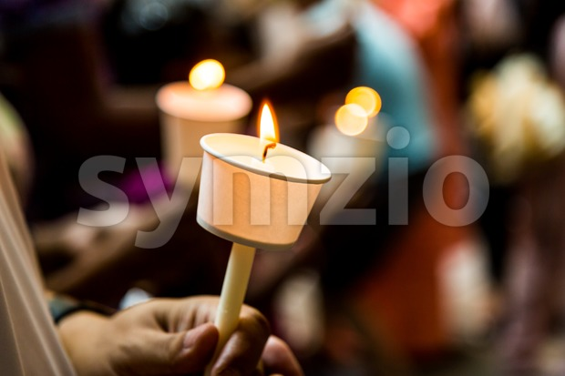Closeup of people holding candle vigil in dark seeking hope Stock Photo