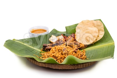 Delicious nasi briyani meal with mutton, dhal on banana leaf Stock Photo
