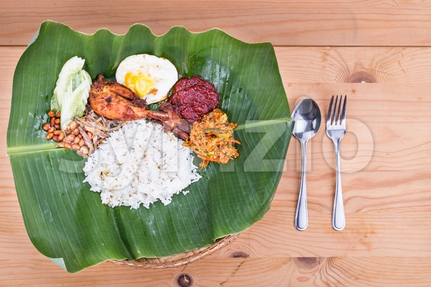 Traditional nasi lemak meal on banana leaf with fried chicken, anchovies, groundnuts, fried eggs, acar and cucumber. Popular cuisine in ...