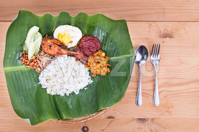 Traditional nasi lemak cuisine on banana leaf with fried chicken Stock Photo