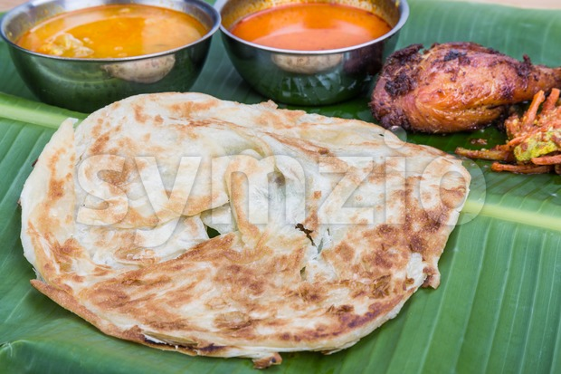 Traditional roti prata served on banana leaf with curry dhal. Stock Photo