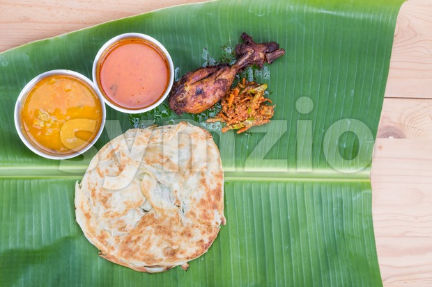 Traditional roti prata served on banana leaf with curry, dhal, fried chicken and acar. Popular cuisine in Malaysia and Singapore.