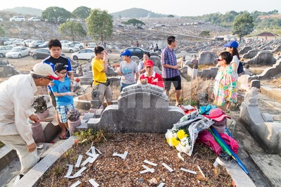 KUALA LUMPUR, MALAYSIA, April 2, 2016: Chinese descendants cleaning tomb and offering prayers to ancestors during the annual QingMing, or tomb Stock Photo