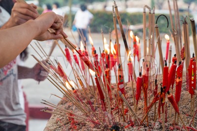 Chinese taoist devotee lighting up candles at temple Stock Photo