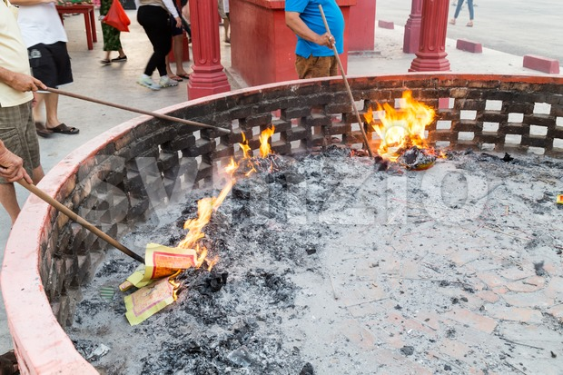 Chinese devotees burning paper offerings during QingMing celebration Stock Photo