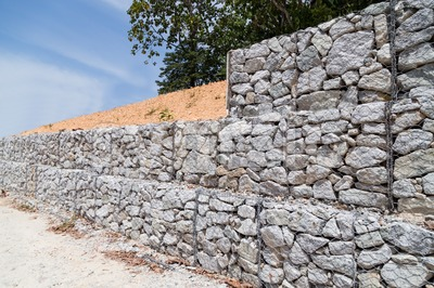 Slope retention management with rocks and wire mesh cage system Stock Photo