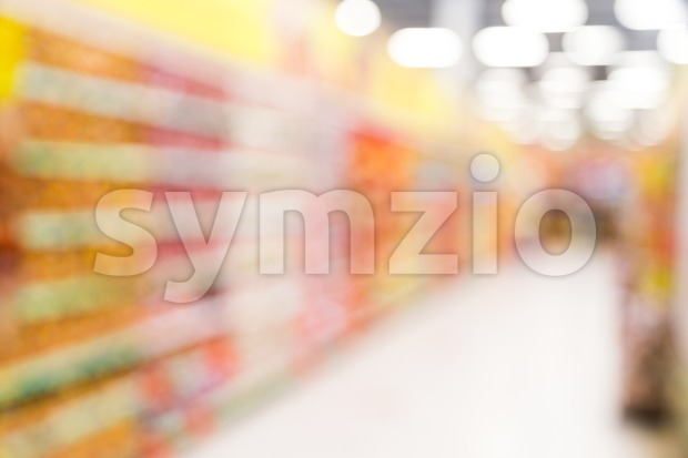 Defocused, long brightly lit  colorful grocery aisle in a modern hypermarket store