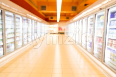 Defocused brightly lit frozen food aisle in modern supermarket Stock Photo