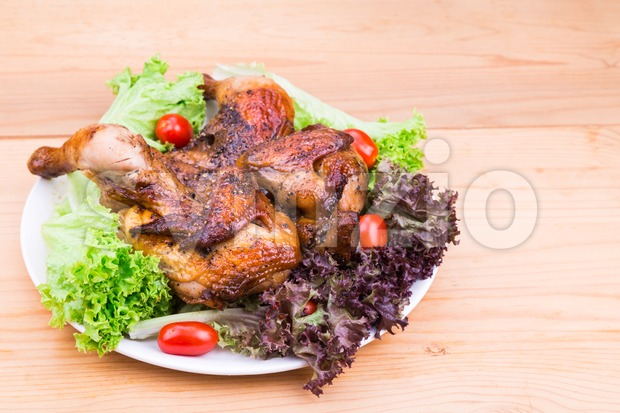 Juicy grilled roast chicken with herb, salad and tomato garnish Stock Photo