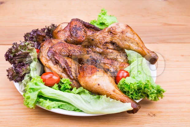 Juicy grilled roast whole chicken with herb, lettuce and tomato garnish on wooden table