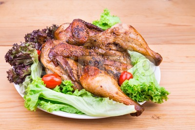 Juicy grilled roast chicken with herb, lettuce and tomato garnish Stock Photo