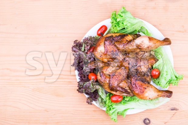 Juicy grilled roast whole chicken with herb, salad and tomato garnish on wooden table