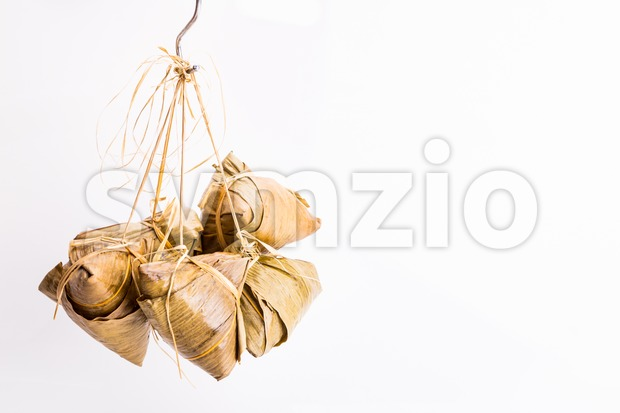Bunch of Chinese rice dumpling or zongzi tied hanging against white background