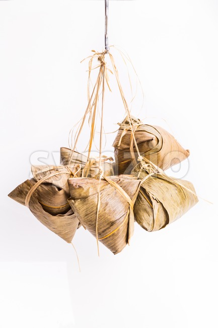 Bunch of Chinese rice dumpling tied hanging against white background Stock Photo