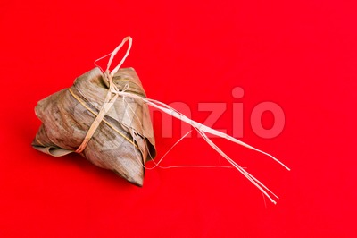 Fresh Chinese rice dumpling or zongzi against red background Stock Photo