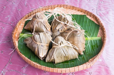 Bunch of Chinese rice dumpling placed on traditional rattan tray Stock Photo