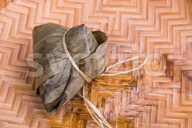Freshly prepared Chinese rice dumpling or zongzi placed on traditional rattan tray