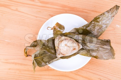 Freshly prepared Chinese rice dumpling or zongzi unwrapped on plate Stock Photo