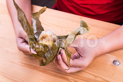 Hand unwrapping Chinese rice dumpling or zongzi on table Stock Photo
