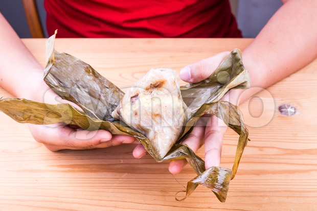 Hand unwrapping freshly cooked Chinese rice dumpling or zongzi on table