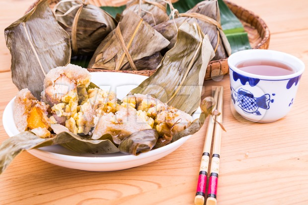 Steamed Chinese rice dumpling or zongzi served on plate with oriental tea