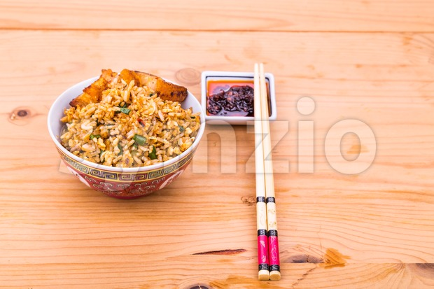 Delicious Chinese spicy fried rice with roast pork in bowl served on wooden table