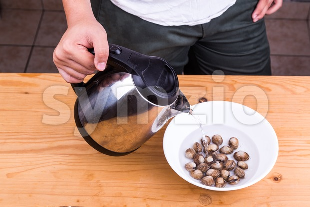 Person pouring boiling water over cockles in bowl Stock Photo
